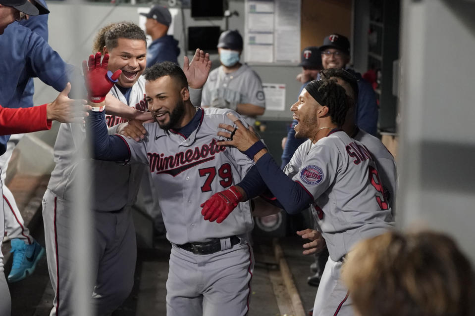 Minnesota Twins' Gilberto Celestino (79) is greeted by teammates Willians Astudillo, left, and Andrelton Simmons, right, after Celestino, who made his major-league debut on June 2, 2021, hit his first MLB career home run during the fourth inning of a baseball game against the Seattle Mariners, Monday, June 14, 2021, in Seattle. His teammates pretended to ignore the rookie until he reached the very end of the dugout and then moved in for the traditional run-scoring congratulations. (AP Photo/Ted S. Warren)