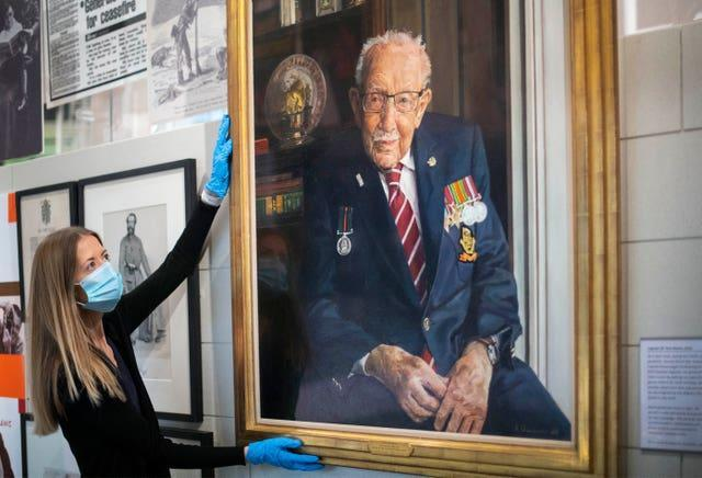A portrait of Captain Sir Tom Moore hangs in the National Army Museum London (Victoria Jones/PA)
