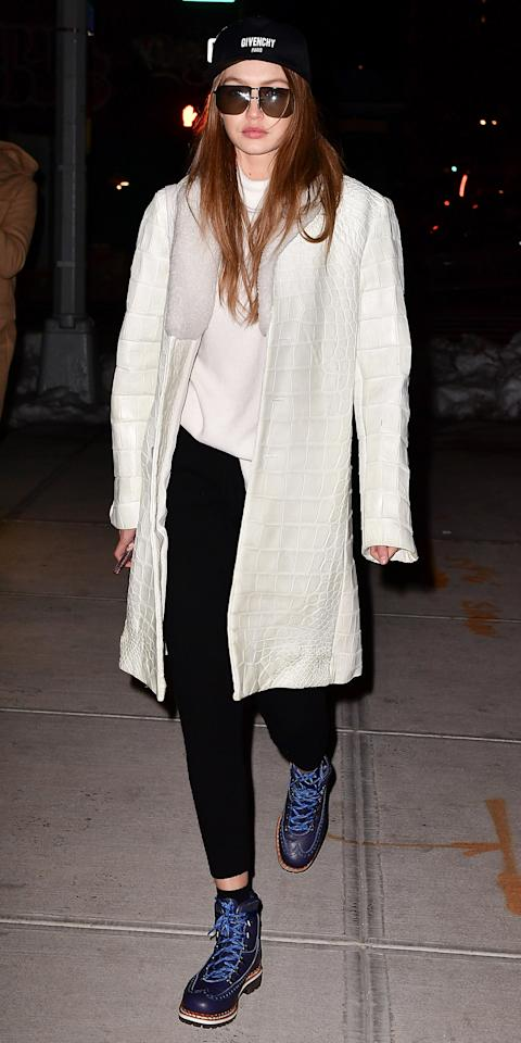 "<p>Hadid kept her white streak post-N.Y.C. snowstorm in a snakeskin-print white jacket, a white turtleneck sweater, and black pants. She finished off the look with a Givenchy hat, oversize sunnies, and blue combat boots (get a similar pair <a rel=""nofollow"" href=""http://www.anrdoezrs.net/links/7799179/type/dlg/sid/ISGigiHadidStreetStyle3.17JA/http://www.zappos.com/p/dr-martens-1460-sea-blue-antique-temperley/product/104730/color/667952"">here</a>).</p>"