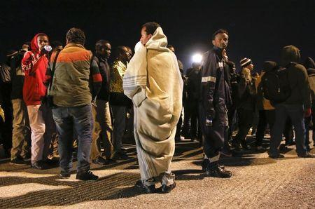 Migrants are disembarked from a navy ship in the Sicilian harbour of Augusta