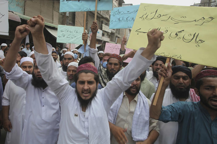 "FILE - In this July 31, 2020 file photo, supporters of a religious group chant slogans with placards that read, ""we can die for honor of Prophet"" at a rally in Peshawar, Pakistan. Ali Hassan is in jail in Paris after allegedly attacking and seriously injuring two people with a meat cleaver in Paris on Sept. 25, 2020. Before the attack, he proclaimed in a video that he was seeking vengeance after the French satirical newspaper Charlie Hebdo republished caricatures of Islam's Prophet Muhammad. In the video Hassan wept and said he had been inspired by teh Tehreek-e-Labbaik party, whose almost sole agenda is to uphold the blasphemy laws, which call for the death penalty against those who offend Islam. (AP Photo/Muhammad Sajjad, File)"
