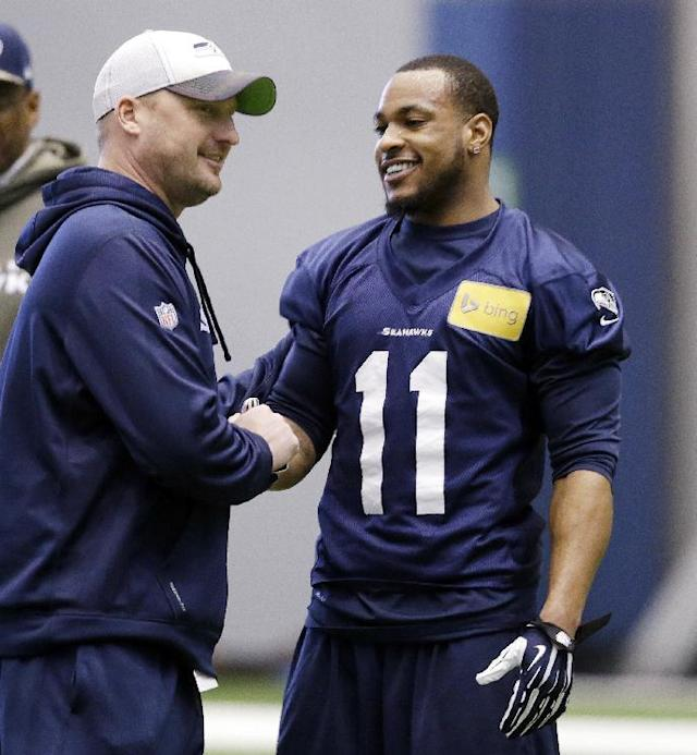 Seattle Seahawks' Percy Harvin (11) shakes hands with special teams coordinator Brian Schneider at NFL football practice Tuesday, Jan. 7, 2014, in Kirkland, Wash. The Seahawks host the New Orleans Saints on Saturday in an NFC divisional playoff game. (AP Photo/Elaine Thompson)