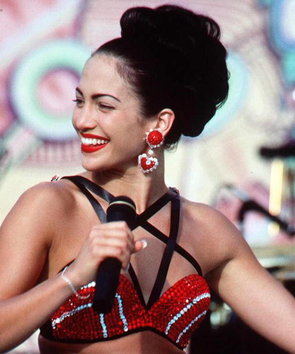 """<h3>1997</h3><br>Who could forget J.Lo's performance in the <em>Selena</em> biopic? We especially love this Quintanilla-inspired high bun and red lip.<span class=""""copyright"""">Photo: SCOTT DEL AMO/AFP/Getty Images.</span>"""