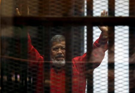 FILE PHOTO: Egypt's deposed president Mohamed Mursi greets his lawyers and people from behind bars at a court wearing the red uniform of a prisoner sentenced to death, during his court appearance with Muslim Brotherhood members on the outskirts of Cairo
