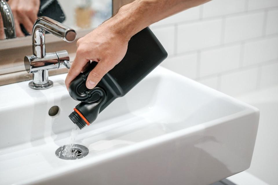 man pouring chemical drain cleaner down a sink