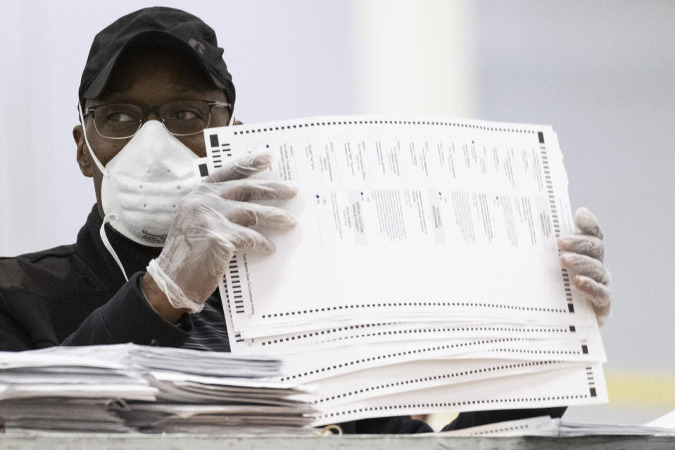 Workers sort and stack ballots in preparation for scanning during a recount, Tuesday, Nov. 24, 2020, in Lithonia, Ga. County election workers across Georgia have begun an official machine recount of the roughly 5 million votes cast in the presidential race in the state. The recount was requested by President Donald Trump after certified results showed him losing the state to Democrat Joe Biden by 12,670 votes, or 0.25% (AP Photo/Ben Gray)