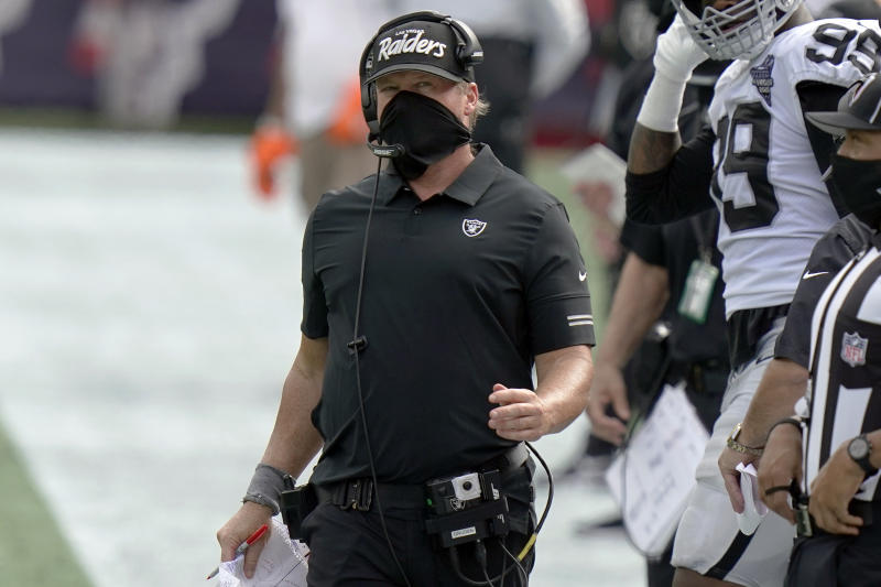 Jon Gruden works along the sideline in the second half wearing a mask that still covers his nose and mouth but no longer covers his neck as it did earlier in the day.