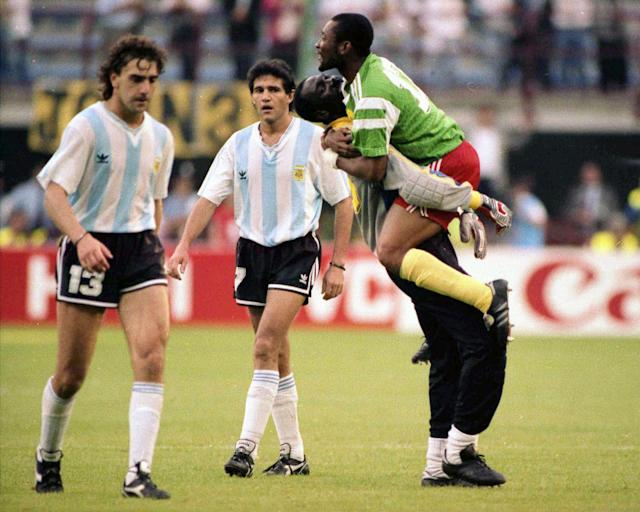FILE - In this June 8, 1990 file photo, dejected Argentine players Nestor Gabriel Lorenzo, left, and Jorge Luis Burruchaga walk off the pitch, past unidentified celebrating Cameroon players, after the opening match of the soccer World Cup, in Milan, Italy. On this day: Opening day in World Cup history has produced its fair share of shocks, not least when Cameroon defeated defending champion Argentina in 1990. (AP Photo/File)