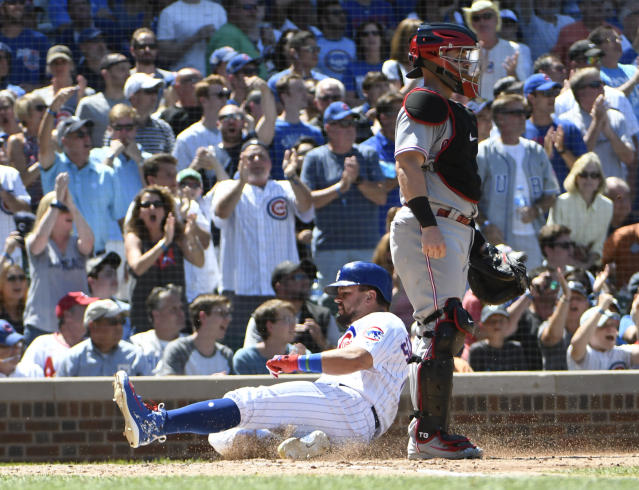 Chicago Cubs' Kyle Schwarber, left, is safe at home as Cincinnati Reds catcher Tucker Barnhart, right, stands nearby during the fourth inning of a baseball game Saturday, July 7, 2018, in Chicago. (AP Photo/David Banks)