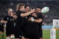 New Zealand's Aaron Smith (9) celebrates with teammates after scoring a try during the Rugby World Cup quarterfinal match at Tokyo Stadium between New Zealand and Ireland in Tokyo, Japan, Saturday, Oct. 19, 2019. (AP Photo/Mark Baker)