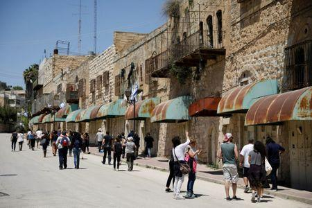 """FILE PHOTO: Visitors on a tour held by leftwing NGO """"Breaking the Silence"""" walk down Shuhada street in the West Bank city of Hebron April 19, 2017. REUTERS/Amir Cohen/File Photo"""