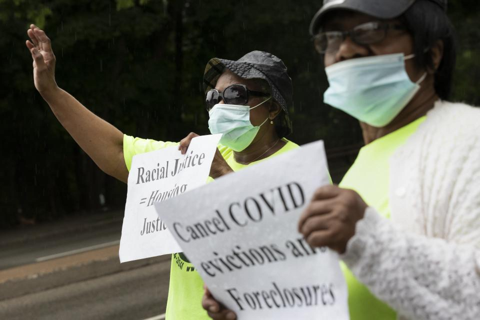 Annie Gordon and Jenny Clark, holding signs and wearing face masks