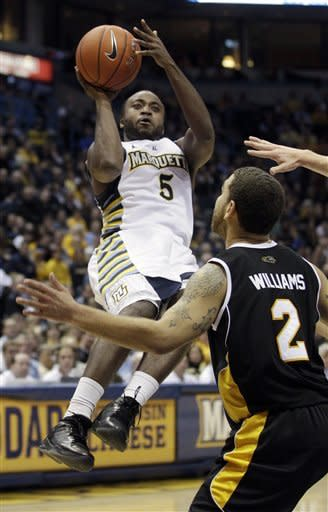 Marquette's Junior Cadougan (5) shoots in front of Wisconsin Milwaukee's Kaylon Williams (2) during the first half of an NCAA college basketball game on Thursday, Dec. 22, 2011, in Milwaukee. (AP Photo/Morry Gash)