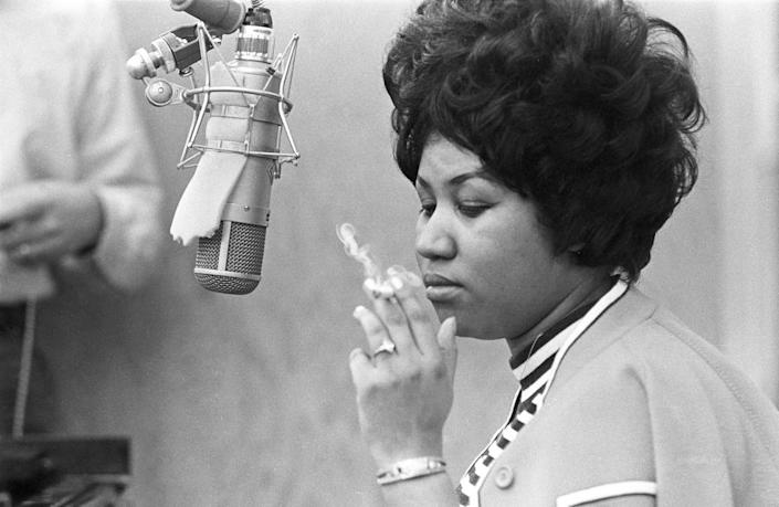 Smoking a cigarette as she works in the studio by a microphone at Muscle Shoals Studios in 1969 in Muscle Shoals, Alabama.