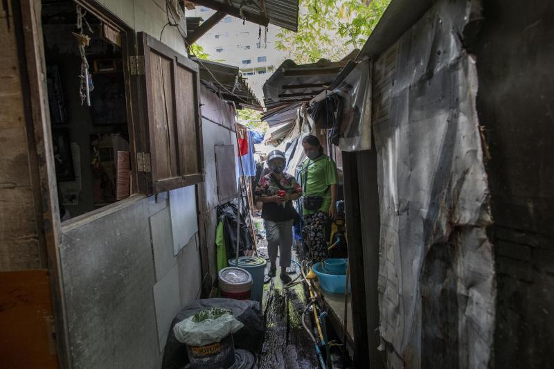Kanyarat Phuankuntod, left, and Jariya Saekean, teachers of Makkasan preschool, walk in a narrow passage after delivering meals for children in Bangkok, Thailand Wednesday, June 24, 2020. During the third month that schools remained closed due to the coronavirus outbreak,  teachers have cooked meals, assembled food parcels and distributed them to families in this community sandwiched between an old railway line and a khlong, one of Bangkok's urban canals. (AP Photo/Gemunu Amarasinghe)