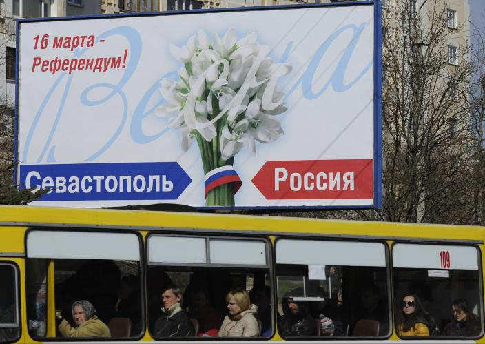 """People ride in a bus by a poster reading """"March 16 - Referendum! Sevastopol. Russia"""" in Sevastopol, Thursday, March 13, 2014. Crimea plans to hold a referendum on Sunday that will ask residents if they want the territory to become part of Russia. Ukraine's government and Western nations have denounced the referendum as illegitimate and warned Russia against trying to annex Crimea. (AP Photo/Andrew Lubimov)"""