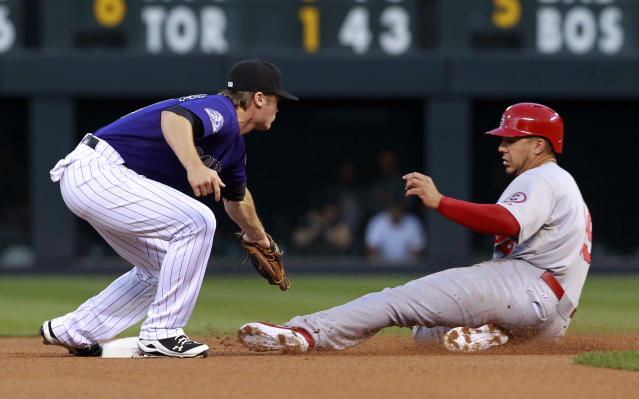 Colorado Rockies second baseman Josh Rutledge, left, prepares to tag St. Louis Cardinals' Jon Jay as he steals second base in the first inning of a baseball game in Denver on Tuesday, Sept. 17, 2013. (AP Photo/David Zalubowski)