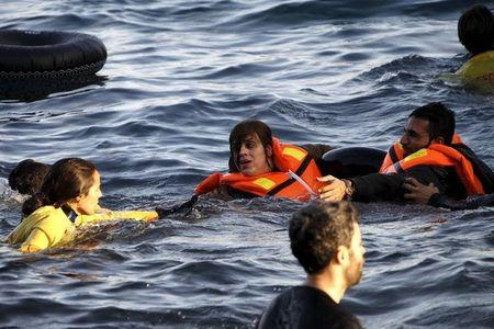 A volunteer lifeguard helps a refugee as a half-sunken catamaran carrying around 150 refugees, most of them Syrians, arrives after crossing part of the Aegean sea from Turkey on the Greek island of Lesbos