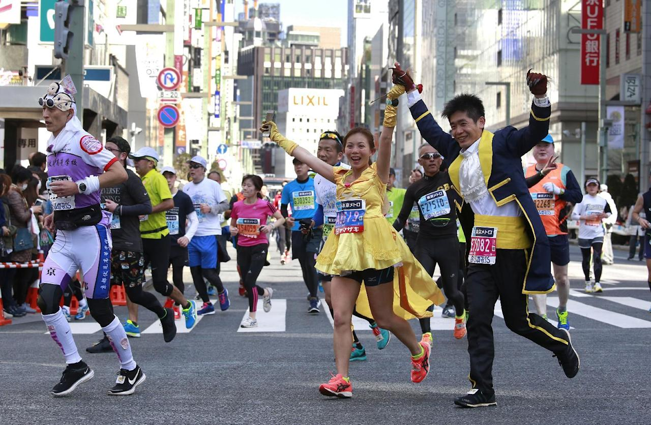 A couple in matching costumes make their way in Tokyo's Ginza shopping district with other runners during the Tokyo Marathon, Sunday, Feb. 26, 2017. (AP Photo/Shizuo Kambayashi)
