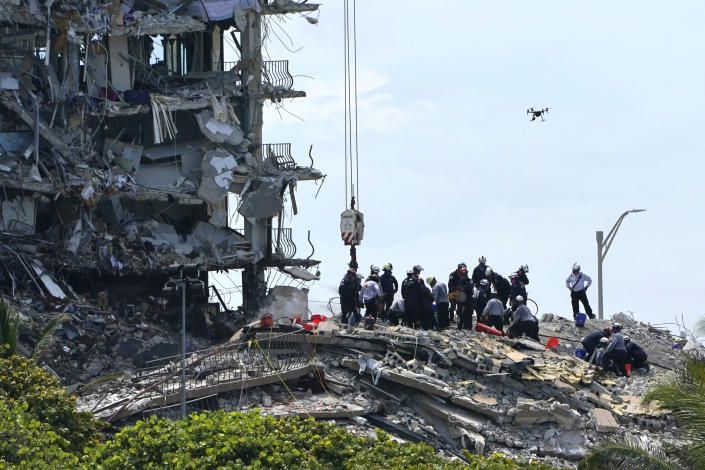 Rescue workers search in the rubble for survivors at the Champlain Towers South condominium, Saturday, June 26, 2021, in the Surfside area of Miami. The building partially collapsed on Thursday. (AP Photo/Lynne Sladky)
