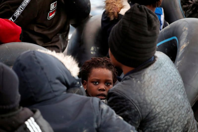 FILE PHOTO: Migrants are seen on a dinghy following a failed attempt to cross to the Greek island of Lesbos as a Turkish Coast Guard boat aproaches them on the waters of the North Aegean Sea, off the shores of Canakkale