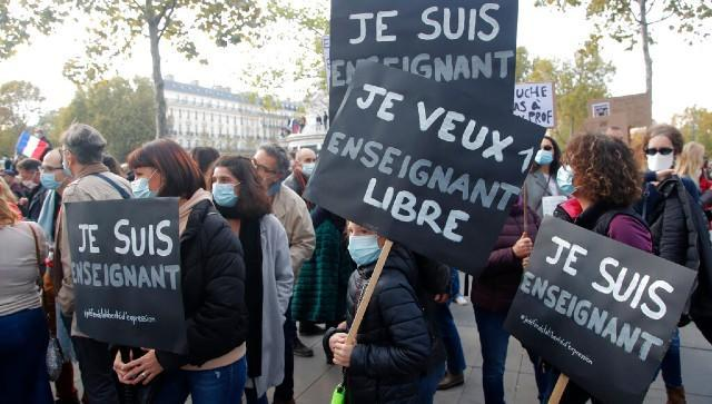 """Demonstrators hold placards reading """"I am a teacher"""" during a demonstration in Paris in support of freedom of speech and to pay tribute to a French history teacher who was beheaded near Paris after discussing caricatures of Islam's Prophet Muhammad with his class. AP"""