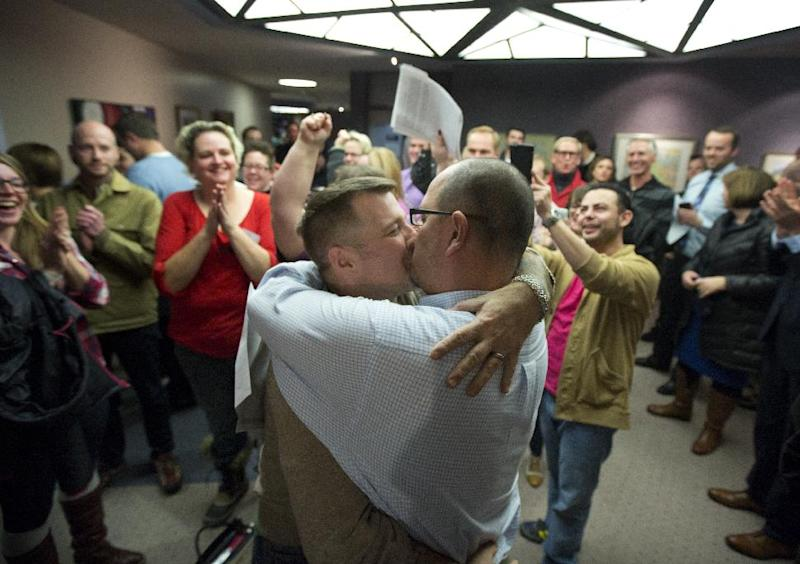 Chris Serrano, left, and Clifton Webb kiss after being married, as people wait in line to get licenses outside of the marriage division of the Salt Lake County Clerk's Office in Salt Lake City, Friday, Dec. 20, 2013. A federal judge ruled on Friday that Utah's ban on same-sex marriage is unconstitutional. (AP Photo/Kim Raff)