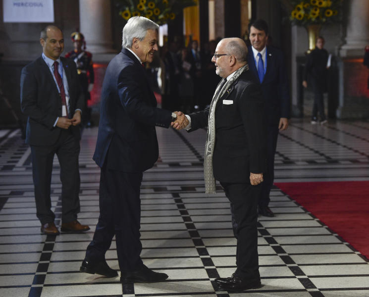 Chile's President Sebastian Pinera, center, is received by Argentina's Foreign Minister Jorge Faurie at the Mercosur Summit in Santa Fe, Argentina, Wednesday, July 17, 2019. The South American trading bloc that includes founding members Brazil, Argentina, Paraguay, and Uruguay, is one of the world's largest. (AP Photo/Gustavo Garello)