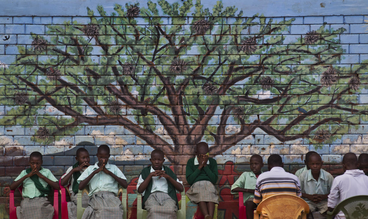 FILE - In this Wednesday, Nov. 21, 2012 file photo, children attend an outdoor Christian prayer session in front of a mural on the side of the meeting hall in the village of Nyumbani which caters to children who lost their parents to HIV, and grandparents who lost their children to HIV, with the bookend generations taking care of one another, in Kenya. U.S. President Donald Trump's move a year ago to dramatically expand cuts in U.S. funding to foreign organizations providing abortion services has left impoverished women around the world without access to treatment for HIV, tuberculosis, and malaria, health groups say. (AP Photo/Ben Curtis, File)