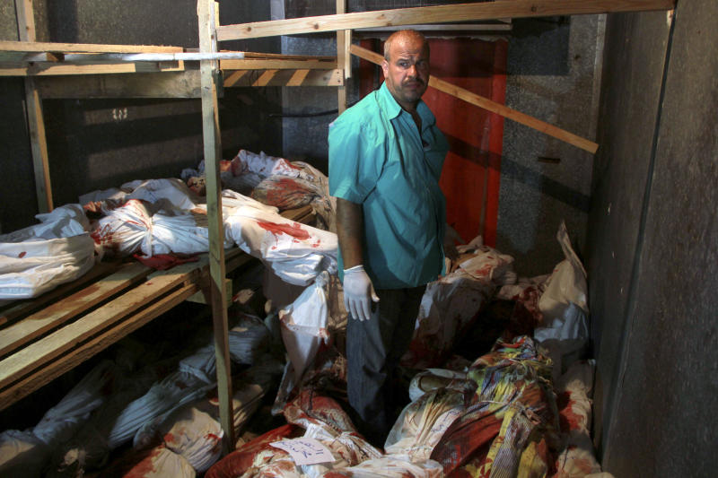 FILE - In this Aug. 2, 2014 file photo, a medic stands among lifeless bodies of people killed in the Gaza war that are stored in a food refrigerator as the town's morgue has run out of space in Rafah, southern Gaza Strip. The Israeli military said on Wednesday Aug. 15, 2018, its investigation focused on an Aug. 1, 2014, battle in the southern Gaza town of Rafah, one of the bloodiest incidents of the 2014 war in the Gaza Strip, has found no criminal wrongdoing by Israeli forces, although human rights advocates accused the military of a whitewash.(AP Photo/Hatem Ali, File)