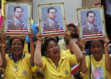 Well-wishers hold up pictures of Thailand's King Bhumibol Adulyadej at Siriraj Hospital in Bangkok