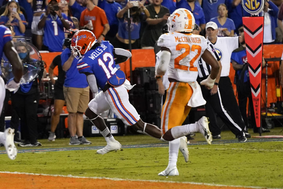 Florida wide receiver Rick Wells (12) runs past Tennessee defensive back Jaylen McCollough (22) on his way to a touchdown off a 9-yard pass play during the second half of an NCAA college football game, Saturday, Sept. 25, 2021, in Gainesville, Fla. (AP Photo/John Raoux)