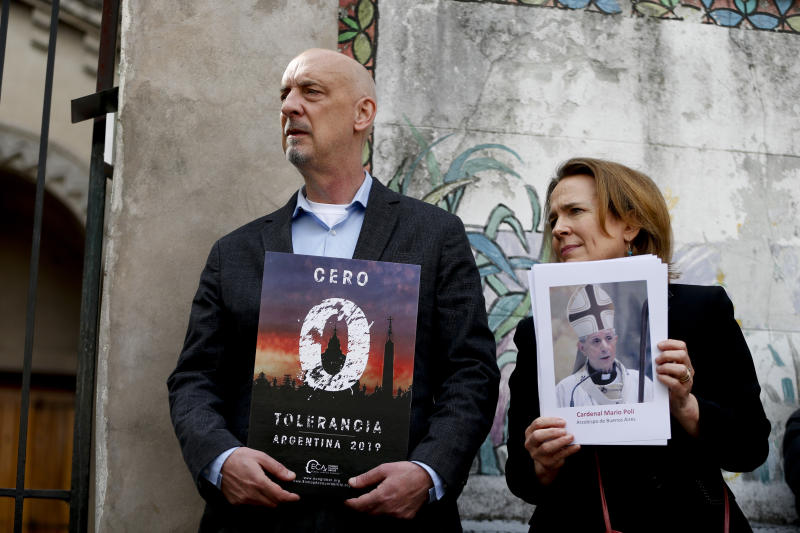 "Anne Barrett Doyle, co-founder of the online research database BishopAccountability.org, holds a picture of Buenos Aires Archbishop Mario Poli, right, next to Peter Isely, member of the organization called Ending Clergy Abuse holding a sign that reads in Spanish: ""Zero tolerance Argentina 2019"" outside a church in Buenos Aires, Argentina, Thursday, May 2, 2019. The two, with others, are demanding Buenos Aires Archbishop Mario Poli have a ""zero tolerance"" policy regarding abuse and put an end to what they see as cover ups by members of the church. (AP Photo/Natacha Pisarenko)"