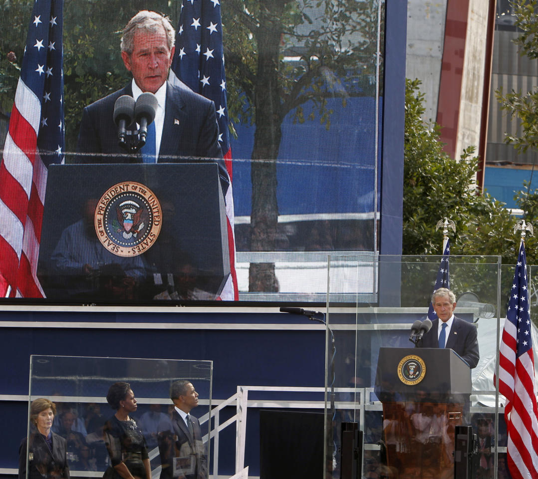 Former President George W. Bush, far right, speaks to friends and relatives of the victims of 9/11 as former first lady Laura Bush, from left, first lady Michelle Obama and President Barack Obama listen during a ceremony marking the 10th anniversary of the attacks at the National September 11 Memorial at the World Trade Center site Sunday, Sept. 11, 2011, in New York. (AP Photo/Jason DeCrow)