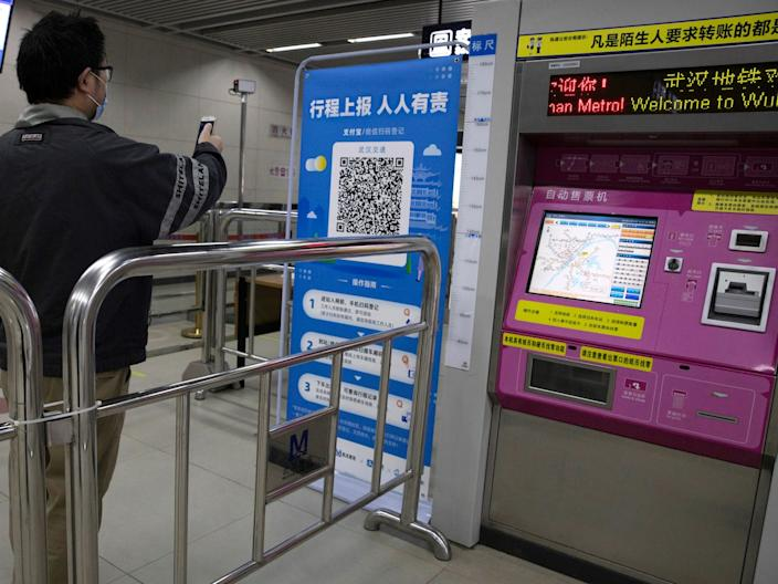 A passenger scans a QR code to get his green pass at a subway station in Wuhan on April 01, 2020.