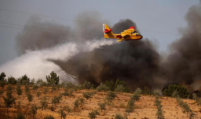 <p>A firefighting plane dumps water on a forest fire next to the village of Macao, near Castelo Branco, Portugal, July 26, 2017. (Rafael Marchante/Reuters) </p>