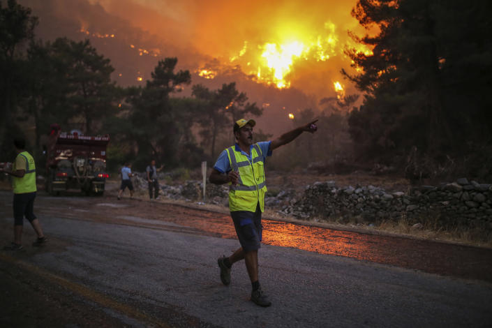 A firefighter points walking away from an advancing fire that rages Cokertme village, near Bodrum, Turkey, Monday, Aug. 2, 2021. For the sixth straight day, Turkish firefighters battled Monday to control the blazes that are tearing through forests near Turkey's beach destinations. Fed by strong winds and scorching temperatures, the fires that began Wednesday have left eight people dead. Residents and tourists have fled vacation resorts in flotillas of small boats or convoys of cars and trucks. (AP Photo/Emre Tazegul)