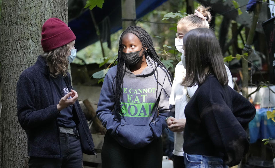 Climate activist Vanessa Nakate from Uganda, 2nd left, visits an activist camp in a forest near the Garzweiler open-cast coal mine in Keyenberg, western Germany, Saturday, Oct. 9, 2021. Garzweiler, operated by utility giant RWE, has become a focus of protests by people who want Germany to stop extracting and burning coal as soon as possible. (AP Photo/Martin Meissner)