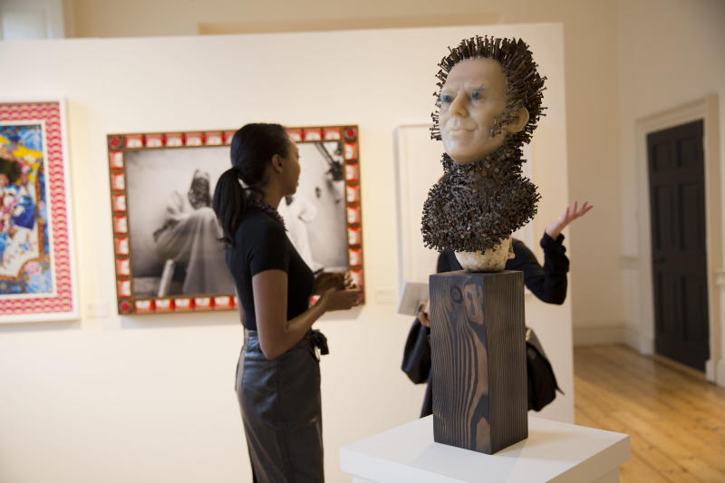"""People talk behind a sculpture by Zak Ove entitled """"White Magic"""", an adapted Madame Tussauds wax work of former British Prime Minister Tony Blair, with plaster skull and a wood base which features in the """"1:54 Contemporary African Art Fair"""" at Somerset House in London, Thursday, Oct. 17, 2013. African tribal art has long been treasured by wealthy Western collectors, but increasingly the continent's contemporary art scene is the one making its presence felt at museums, auction houses and art fairs. London now has four galleries focused on African contemporary art, three of them opening in the past three years. (AP Photo/Matt Dunham)"""