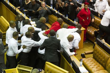 Members of Julius Malema's Economic Freedom Fighters (EFF) (in red) clash with security officials after being ordered out of the chamber during President Jacob Zuma's State of the Nation address in parliament in Cape Town February 12, 2015.  REUTERS/Roger Bosch/Pool