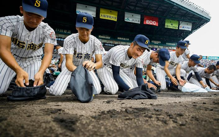 In August 2019, Akashi Commercial High School baseball players collected dirt from the grounds after being defeated at Koshien Stadium in Nishinomiya, western Japan - Kyodo News via AP