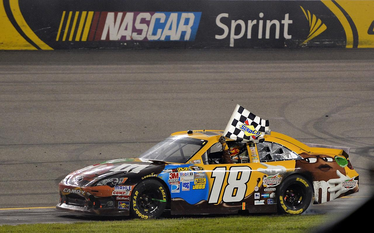 RICHMOND, VA - APRIL 28:  Kyle Busch, driver of the #18 M&M's Ms. Brown Toyota, celebrates with the checkered flag after winning the NASCAR Sprint Cup Series Capital City 400 at Richmond International Raceway on April 28, 2012 in Richmond, Virginia.  (Photo by Drew Hallowell/Getty Images)