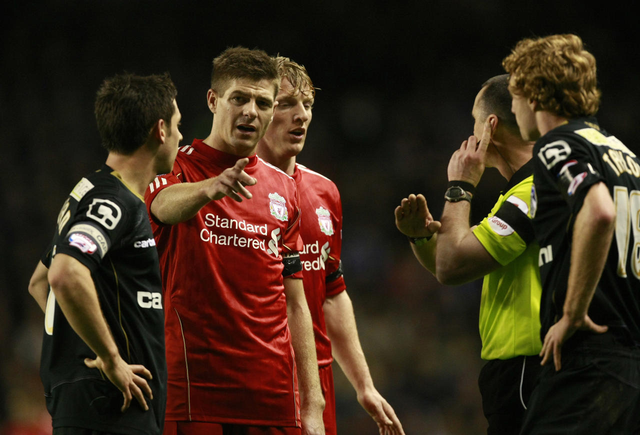 Liverpool's Steven Gerrard, second left, talks with referee Neil Swarbrick after an incident involving Oldham Athletic's Tom Adeyemi, not pictured, and a member of the crowd during their FA Cup third round soccer match at Anfield, Liverpool, England, Friday Jan. 6, 2012. The police are investigating an incident in which a black Oldham player appeared to be the target of abuse from Liverpool fans during an FA Cup third-round match on Friday. Oldham right back Tom Adeyemi was visibly upset late in the game at Anfield after seemingly taking offence from something shouted from the Liverpool-supporting area known as The Kop. (AP Photo/Tim Hales)
