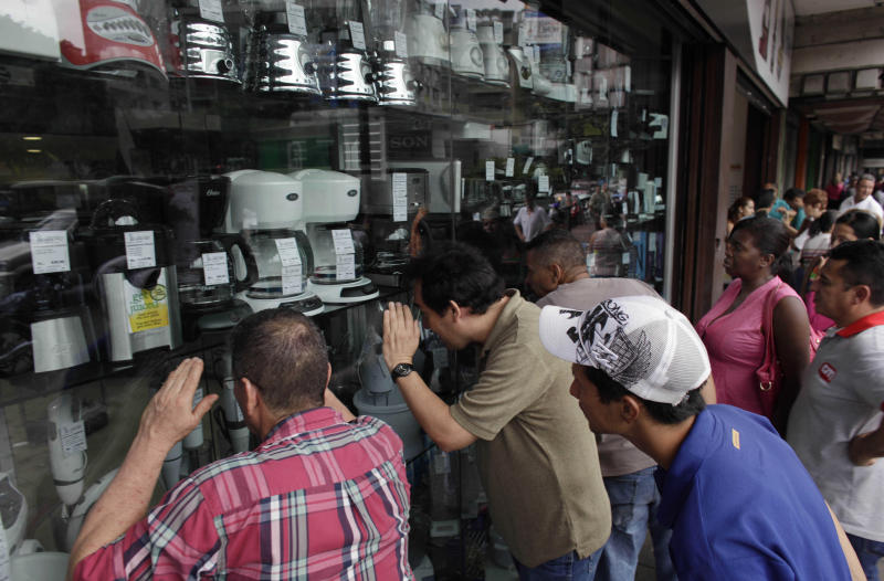 "People peek into the storefront window of an appliance store in Caracas, Venezuela, Monday, Nov. 11, 2013. President Nicolas Maduro seized control of a nationwide chain of appliance stores Friday seeking to battle inflation and shortages. Shoppers were still arriving Monday to join the hundreds who began amassing over the weekend after price inspectors said they found evidence of ""usury"" and Maduro ordered the chain Tiendas Daka ""occupation."" (AP Photo/Ariana Cubillos)"