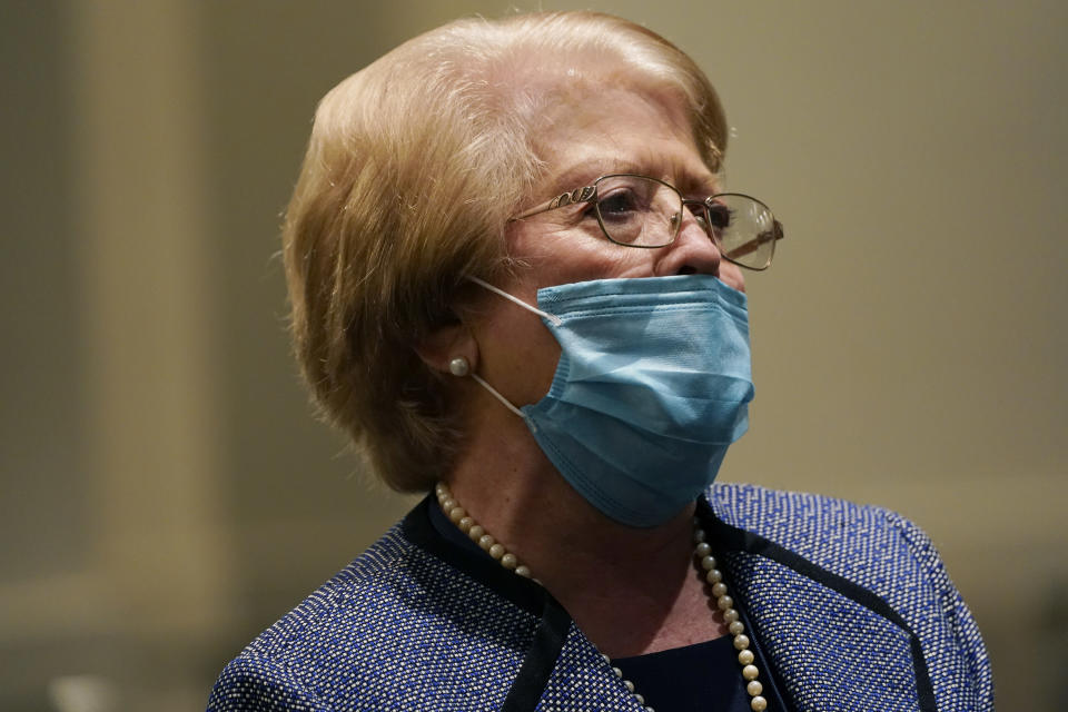 Although face masked, Highland Colony Baptist Church greeter Joy Sartain, prays during services in Ridgeland, Miss., Nov. 29, 2020. The church practices covid protocols by allowing families to sit spaced out from others, separating older and more vulnerable members in the Worship Center and providing sanitizer and masks at the entrance. (AP Photo/Rogelio V. Solis)