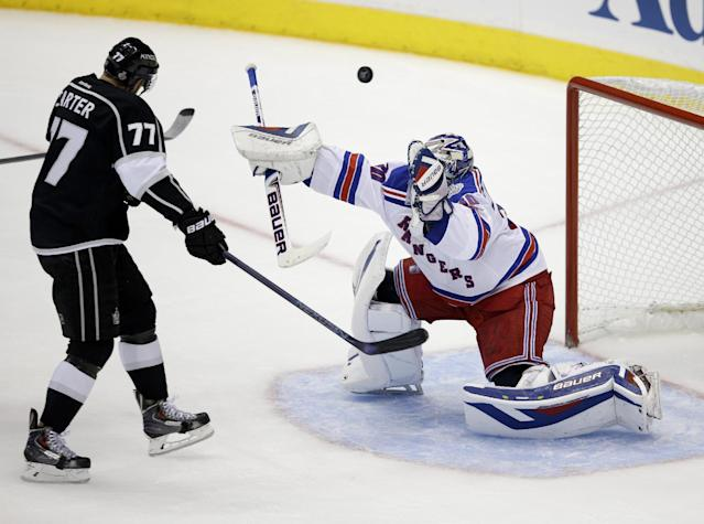 New York Rangers goalie Henrik Lundqvist, of Sweden,, right, blocks a shot by Los Angeles Kings center Jeff Carter during the second period of Game 2 in the NHL hockey Stanley Cup Finals in Los Angeles, Saturday, June 7, 2014. (AP Photo/Jae C. Hong)