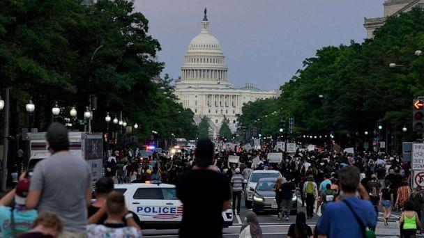 PHOTO: Demonstrators walk along Pennsylvania Avenue as they protest the death of George Floyd, a black man who died in police custody, May 29, 2020, in Washington, D.C. (Evan Vucci/AP)