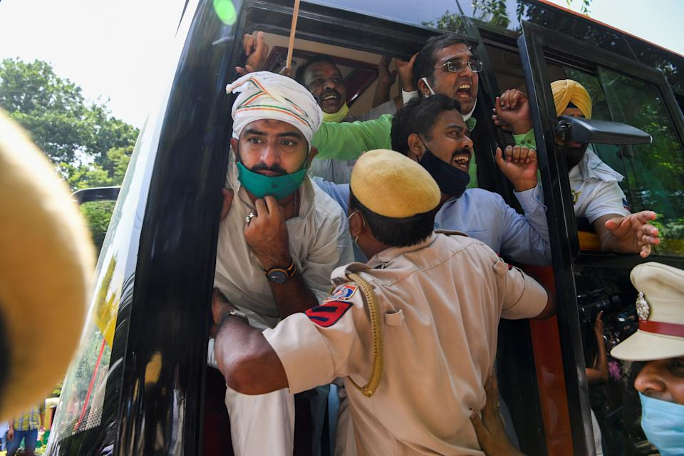 A policeman pushes Congress Party activists into a bus after detaining them during an anti-government demonstration to protest against the recent passing of new farm bills in parliament in New Delhi on September 28, 2020. (Photo by Sajjad HUSSAIN / AFP) (Photo by SAJJAD HUSSAIN/AFP via Getty Images)