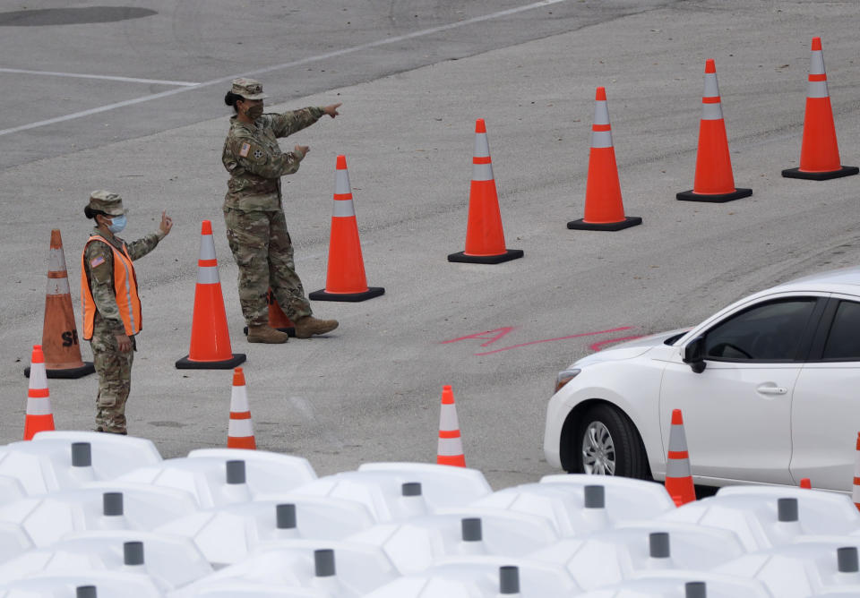 National Guard members direct cars, Wednesday, Aug. 5, 2020, at a COVID-19 testing site outside Hard Rock Stadium in Miami Gardens, Fla. State officials say Florida has surpassed 500,000 coronavirus cases. Meanwhile, testing is ramping up following a temporary shutdown of some sites because of Tropical Storm Isaias. (AP Photo/Wilfredo Lee)