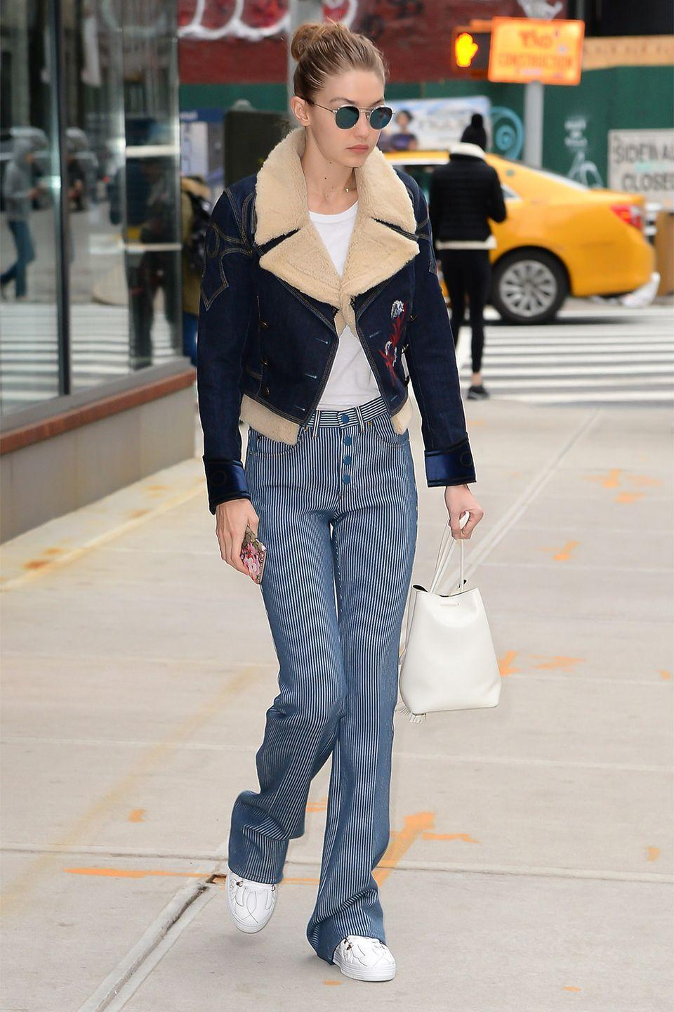 <p>In a denim shearling jacket, white tee, high-waisted blue pinstriped flare pants, white sneakers, a white bucket bag and Krewe sunglasses while out in NYC.</p>